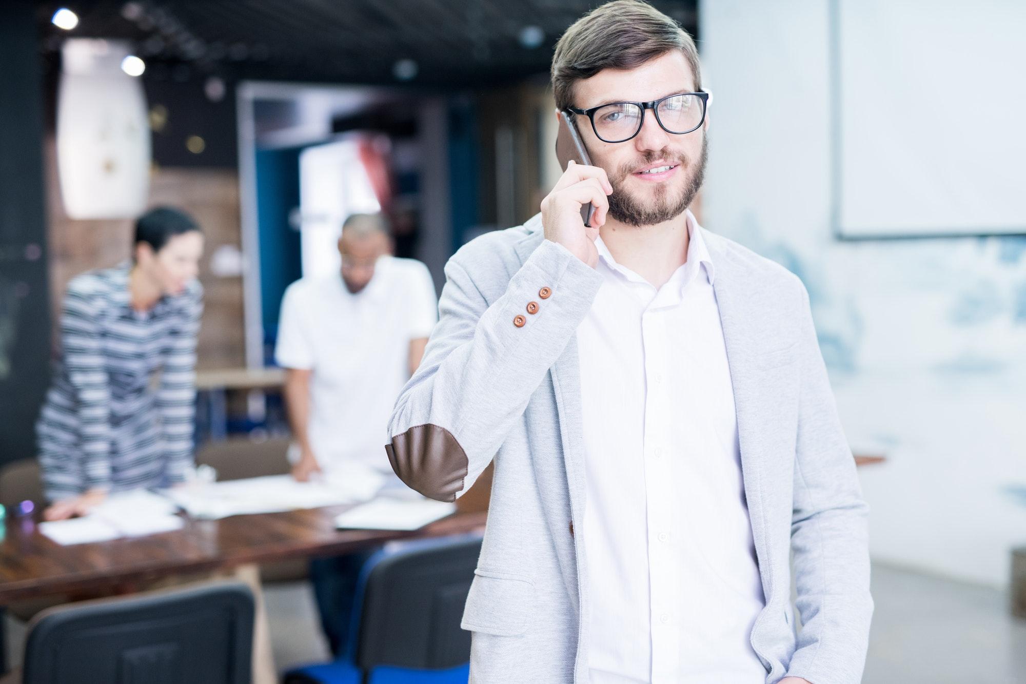 Handsome sales manager calling customer